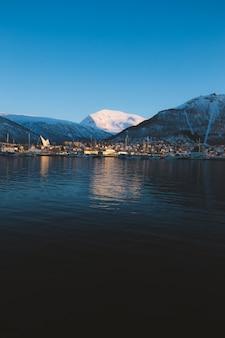 Tir vertical d'un lac entouré de montagnes couvertes de neige à tromso, norvège
