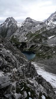 Tir vertical d'un lac entouré de montagnes sous un ciel nuageux