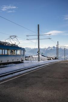 Tir vertical d'une ligne aérienne à côté de la voie ferrée d'un train électrique sous un ciel bleu clair