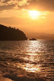 Tir vertical de la mer entourée de montagnes au coucher du soleil