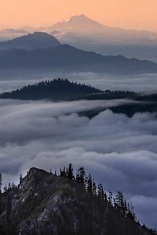 Tir vertical de montagnes au-dessus des nuages avec un ciel orange