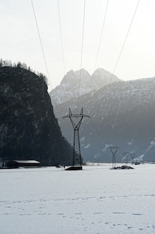 Tir vertical des montagnes couvertes de neige en hiver par un jour brumeux