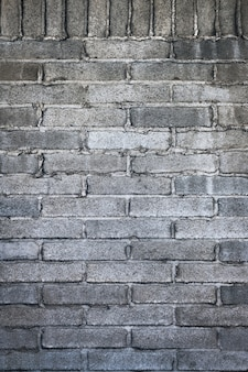 Tir vertical d'un mur de briques gris avec du ciment