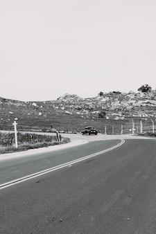 Tir vertical en niveaux de gris d'une route de campagne