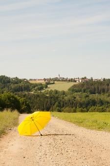 Tir vertical d'un parapluie jaune ouvert sur la route dans la campagne