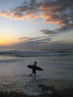 Tir vertical d'une personne tenant une planche de surf marchant près d'une mer ondulée pendant le coucher du soleil