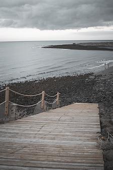 Tir vertical d'une plage avec un pont en bois sous un ciel nuageux