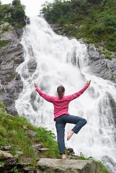 Tir vertical d'une randonneuse pratiquant le yoga devant la belle cascade dans les montagnes