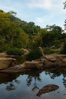 Tir vertical d'une rivière avec des rochers à la falaise des cascades de ba ho au vietnam