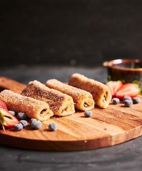 Tir vertical de rouleaux de pain grillé aux fruits rouges sur une plaque en bois avec un fond noir