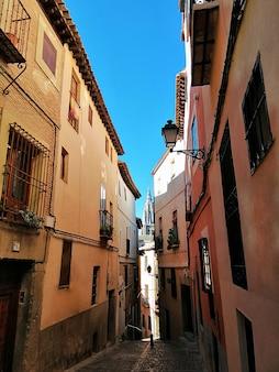 Tir vertical d'une rue étroite avec des bâtiments courts colorés à tolède, espagne