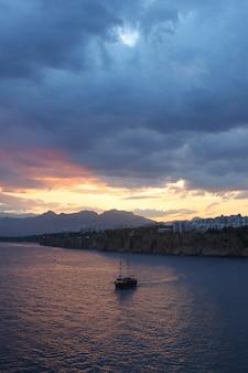 Tir vertical d'un seul bateau sur la mer sous les nuages sombres au coucher du soleil