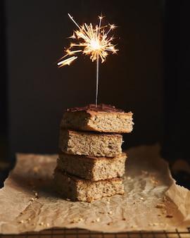 Tir vertical d'un tas de délicieux gâteaux aux noix avec glaçage au chocolat et étincelles sur le dessus
