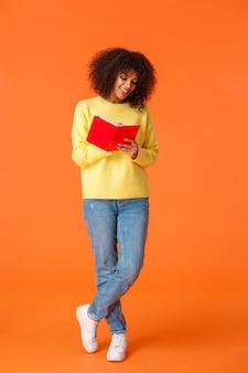Tir vertical sur toute la longueur d'une étudiante afro-américaine mignonne rêveuse avec coupe de cheveux afro, vêtements décontractés, aller à l'université, prendre des notes, debout sur un mur orange et écrire dans un cahier en souriant.