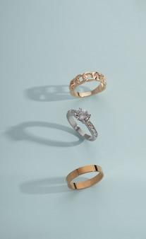 Tir vertical de trois anneaux d'or sur fond bleu avec espace de copie