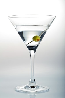 Tir vertical d'un verre de martini et une olive dedans sur blanc