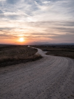 Tir vertical d'une voie dans un champ herbeux avec la vue imprenable sur le coucher du soleil dans le