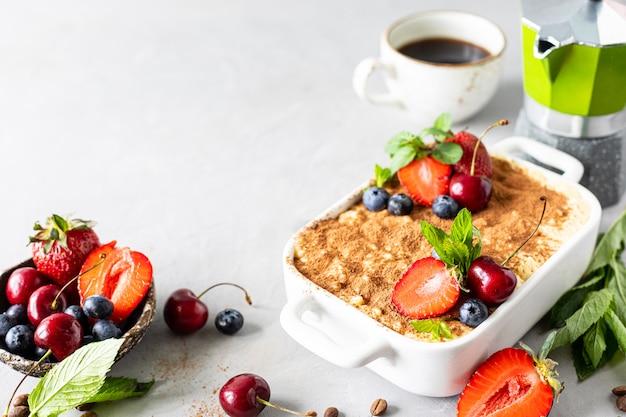 Tiramisu dessert italien classique décoré de fraises, cerises et menthe sur fond blanc. copiez l'espace pour votre texte.