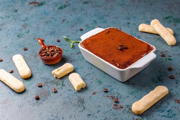 Tiramisu dessert italien traditionnel dans une assiette en céramique, vue de dessus.