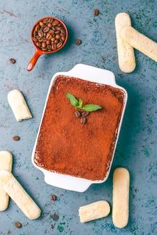 Tiramisu dessert italien traditionnel dans une assiette en céramique, vue du dessus.