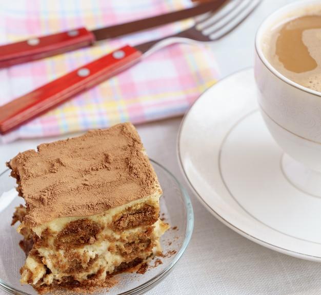 Tiramisu gâteau sur une assiette avec une tasse de thé sur le fond.
