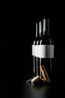Tire-bouchon et bouchons de liège près des bouteilles de vin