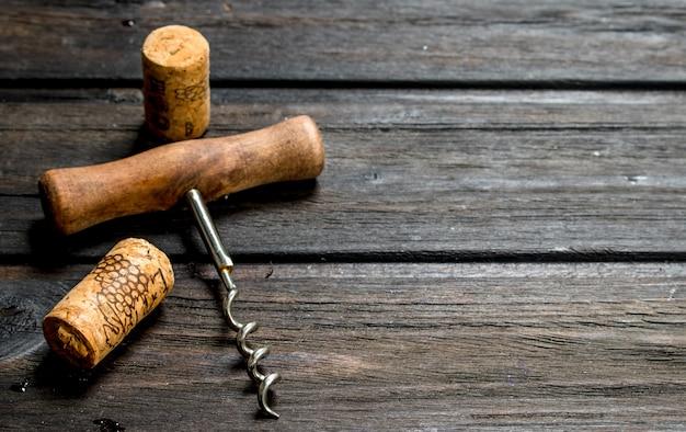 Tire-bouchon avec des bouchons. sur une surface en bois.