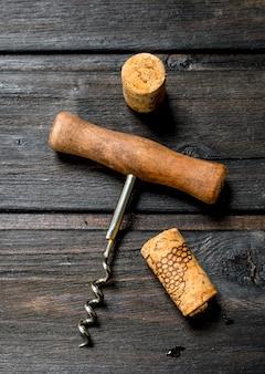 Tire-bouchon avec des bouchons sur une table en bois.