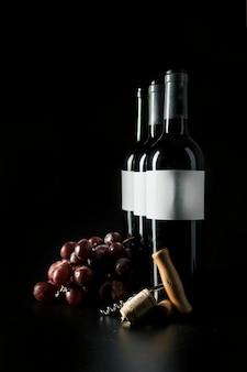 Tire-bouchon et raisin près des bouteilles de vin