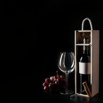 Tire-bouchon et raisin près de verre à vin et bouteille