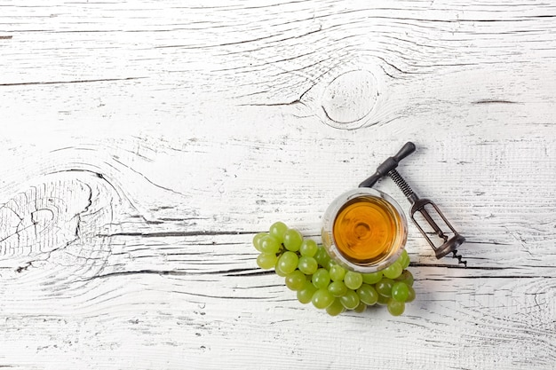 Tire-bouchon, raisin et verre à vin sur fond de planche de bois blanc