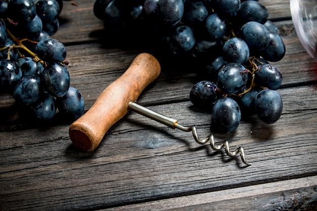 Tire-bouchon avec raisins noirs sur une table en bois.