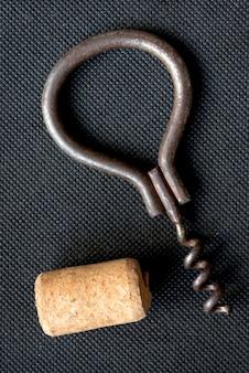 Tire-bouchon rouillé vintage avec bouchon de vin sur fond sombre