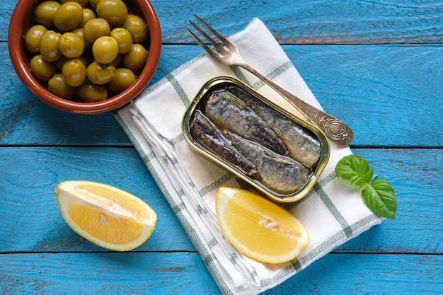 Tiré d'en haut d'une boîte de sardines à l'huile, avec quelques feuilles de basilic, quartiers de citron et olives sur une table rustique bleue