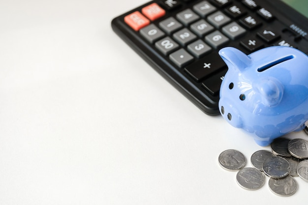 Tirelire bleue, calculatrice et pièces de monnaie