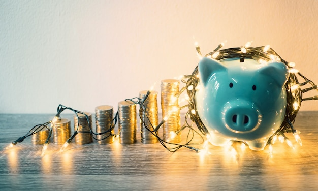 Tirelire bleue avec graphique de croissance des piles de pièces et lumières de fête, économiser de l'argent pour le futur plan d'investissement et le concept de fonds de retraite