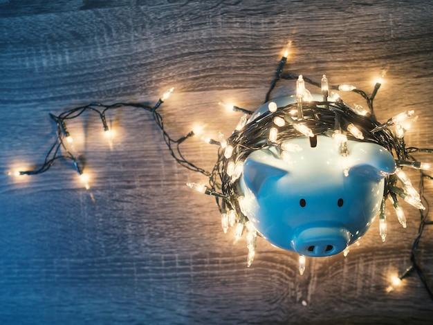Tirelire bleue avec des lumières de fête, profitez d'économies pour le concept de vacances.