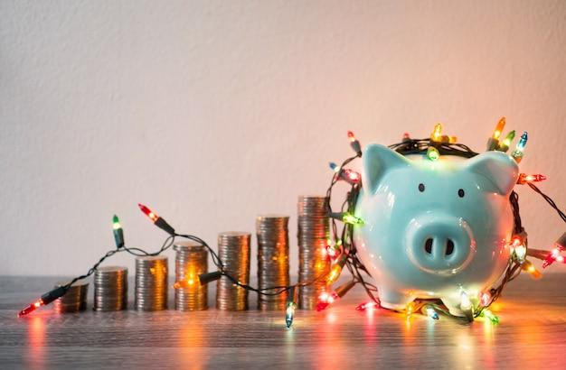 Tirelire bleue avec pile de pièces et lumières de fête économisant de l'argent pour le concept de fonds de retraite