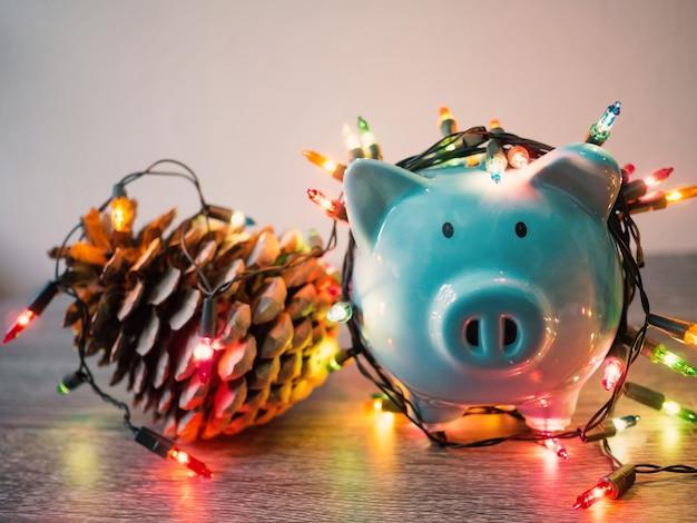Tirelire bleue et pomme de pin avec des lumières de fête, profitez d'économies pour le concept de vacances.