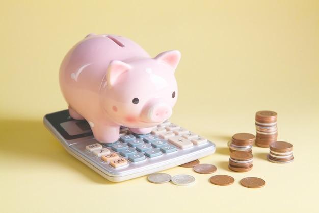 Tirelire, calculatrice et pièces de monnaie sur la table