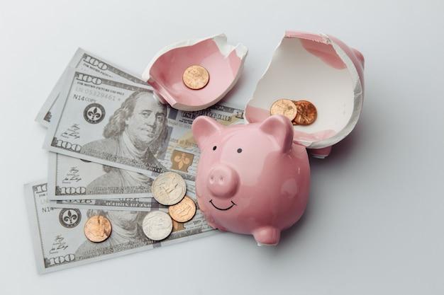 Tirelire cassée avec billets d'un dollar et pièces de monnaie sur fond blanc