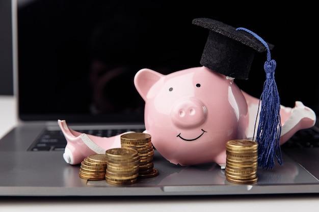 Tirelire cassée en chapeau de graduation sur ordinateur portable. concept d'éducation et de bourse coûteux.