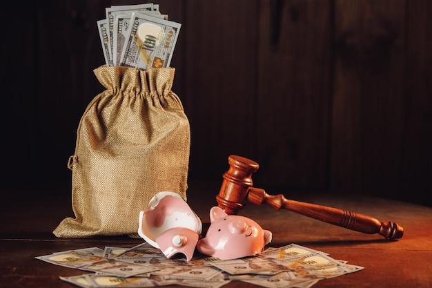 Tirelire cassée avec sac d'argent et juge concept de crise de faillite de marteau