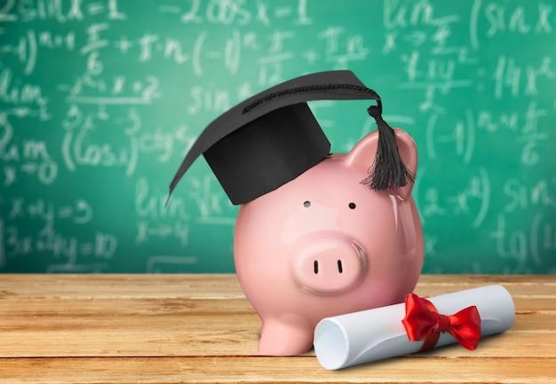 Tirelire avec chapeau de graduation et diplôme