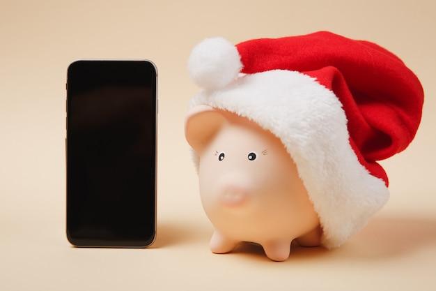 Tirelire avec chapeau de noël, téléphone portable avec écran vide vide isolé sur fond beige. investissement d'accumulation d'argent, services bancaires, concept de richesse. copiez la maquette publicitaire de l'espace.