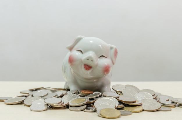 Tirelire cochon blanc et pièces d'argent sur table en bois.concept de finance et d'économie d'argent, d'investissement ou d'âge de la retraite à l'avenir.