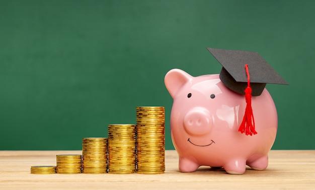 Tirelire dans un chapeau diplômé près d'une pile de pièces économies pour l'éducation prix de l'enseignement supérieur