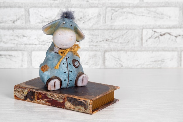 Tirelire décorative d'âne de jouet en céramique sur un vieux livre