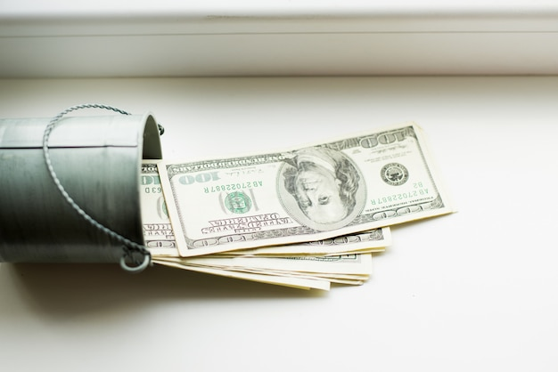 Tirelire, dollars dans le seau sur la fenêtre blanche.