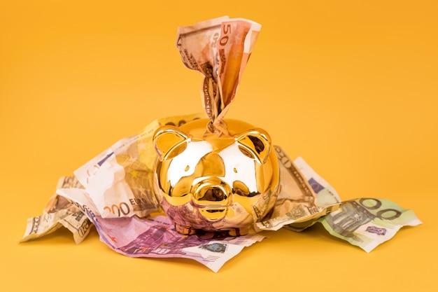 Tirelire dorée avec billets en euros sur fond jaune